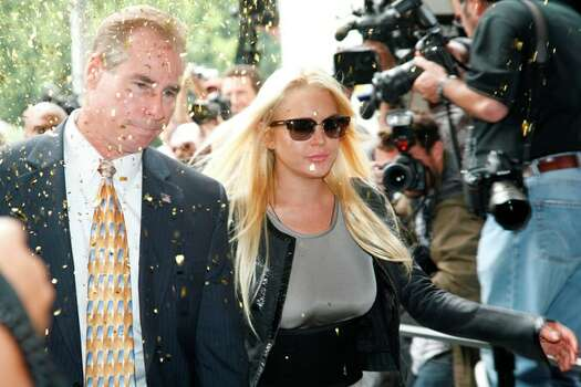 Amid a stream of confetti, actress Lindsay Lohan arrives with an official to court in Beverly Hills, Calif., Tuesday to begin her 90 day jail sentence for violating the terms of her probation.