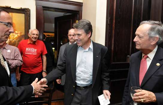 Gov. Rick Perry speaks to supporters at Maggiano's Little Italy at The Rim in San Antonio. The Republican has challenged President Obama to fix the economy and maintain the nation's borders.