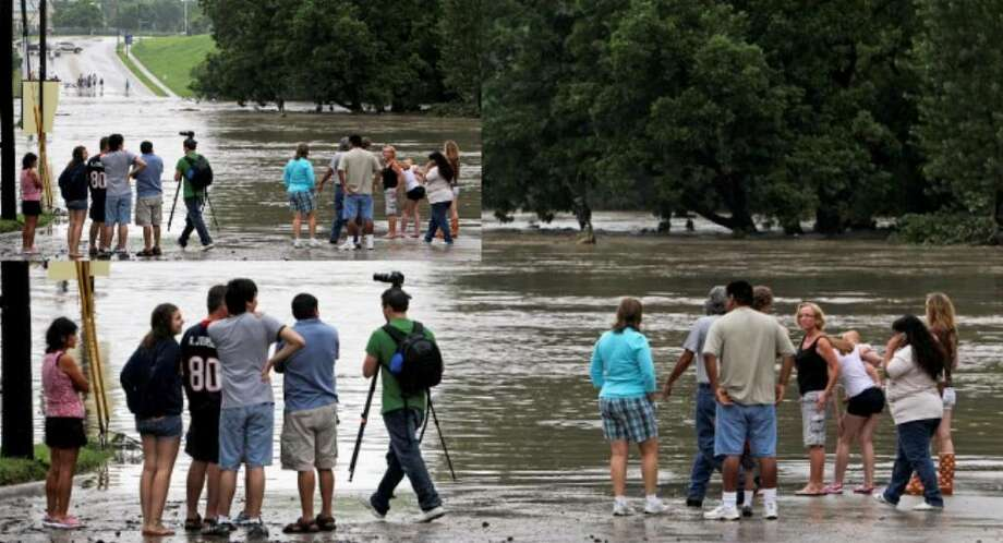 Onlookers check out the flooding Guadalupe River at the Common Street bridge in New Braunfels Wednesday. The New Braunfels Public Library can be seen up the hill at left.