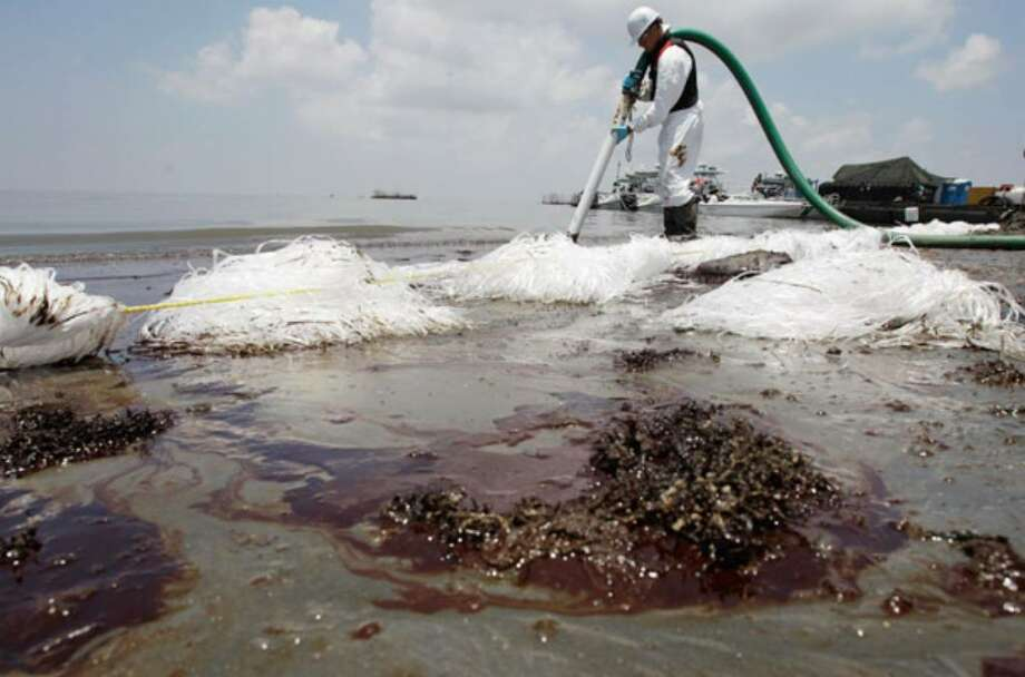 A worker uses a suction hose to remove oil washed ashore from the Deepwater Horizon spill in Belle Terre, La.