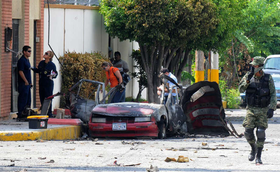 A burned auto apparently sporting Texas license plates is seen in front of the Televisa TV offices in Ciudad Victoria, Mexico, after an explosion.