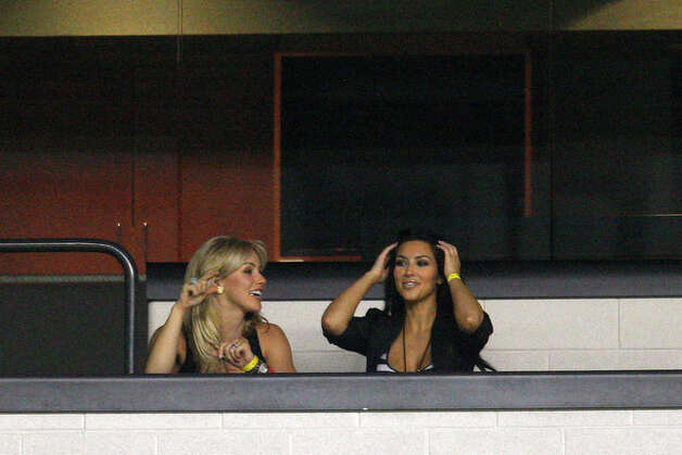 Wide receiver Miles Austin's girlfriend Kim Kardashian, right, and quarterback Tony Romo's girlfriend Candice Crawford sit together in a suite during practice. / glara@express-news.net