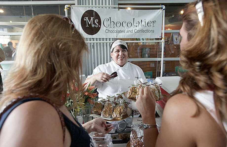 Janie Romo offers samples of her confections to potential customers. The owner of Ms. Chocolatier sells her chocolate treats at the Pearl Farmers Market and other places. She plans to open her own shop. / San Antonio Express-News