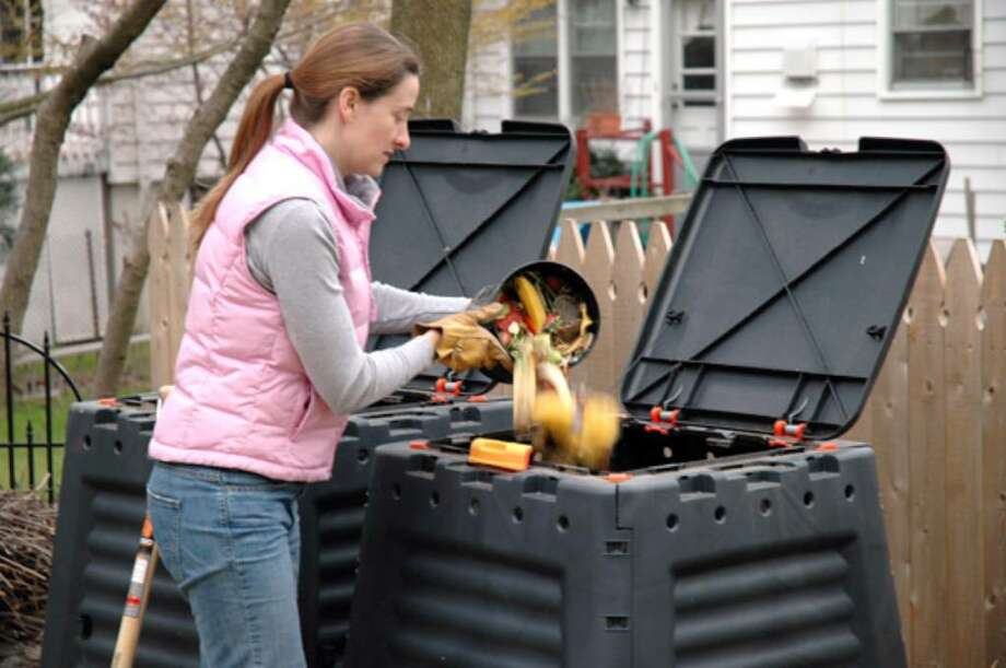 Jennifer Carpenter Jensen dumps food scraps from a container she keeps in her kitchen into a commercially purchased composting bin outside of her home in Larchmont, N.Y.