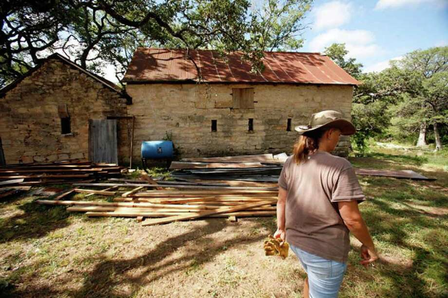 Archaeologist Alexandria Miller walks by a building where she and her crew are digging to find artifacts that they hope will reveal the age and purpose of the structure.