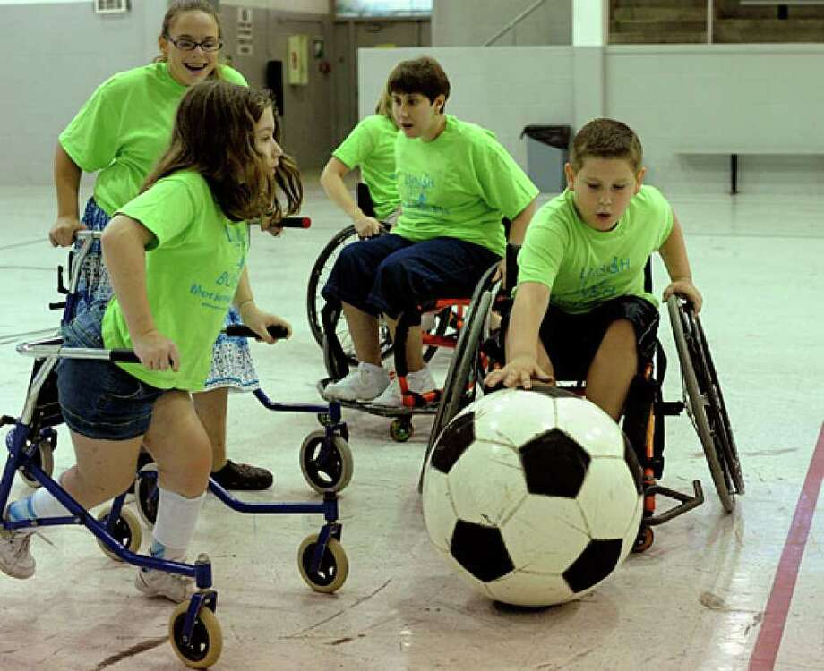 Hunter Simpson, 10, handles the ball during a game of indoor soccer as part of the Spina Bifida Texas Lunch Bunch.