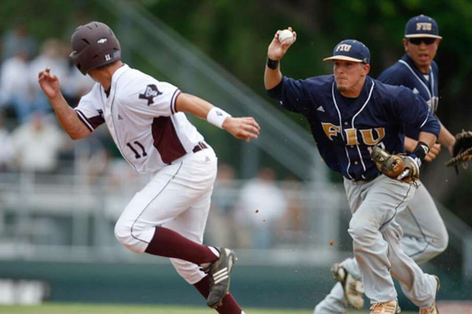 Texas A&M runner Joaquin Hinojosa (11) is chased by Florida International's Junior Arrojo during a first-inning rundown.