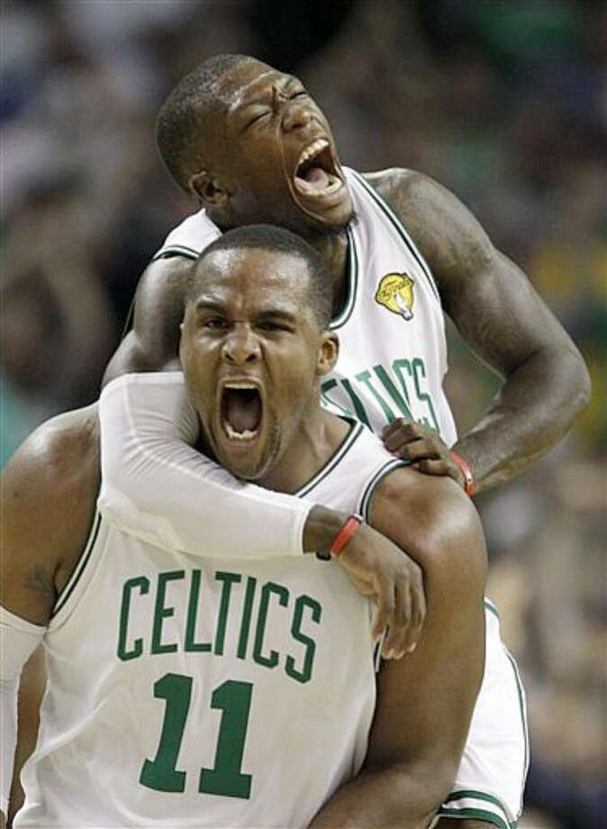 Boston Celtics forward Glen Davis (11) and guard Nate Robinson (top) celebrate a scoring run against the Los Angeles Lakers during the fourth quarter in Thursday's Game 4.