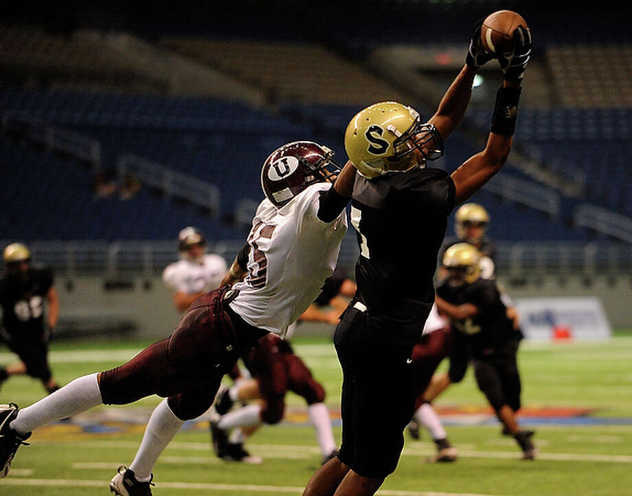 Seguin receiver Ty MIles catches a touchdown pass as Uvalde's Angel Blanco attempts to defend during the first half of the Texas Football Classic.
