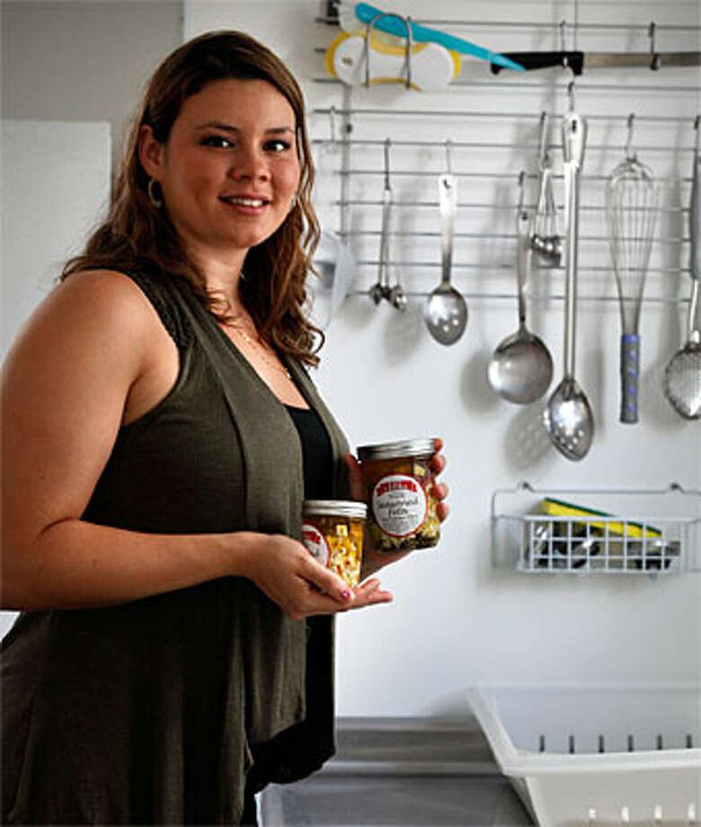 Chrissy Omo holds jars of her CKC Farms products in her cheese room in Blanco. Omo milks her goats twice a day to make a variety of cheeses.