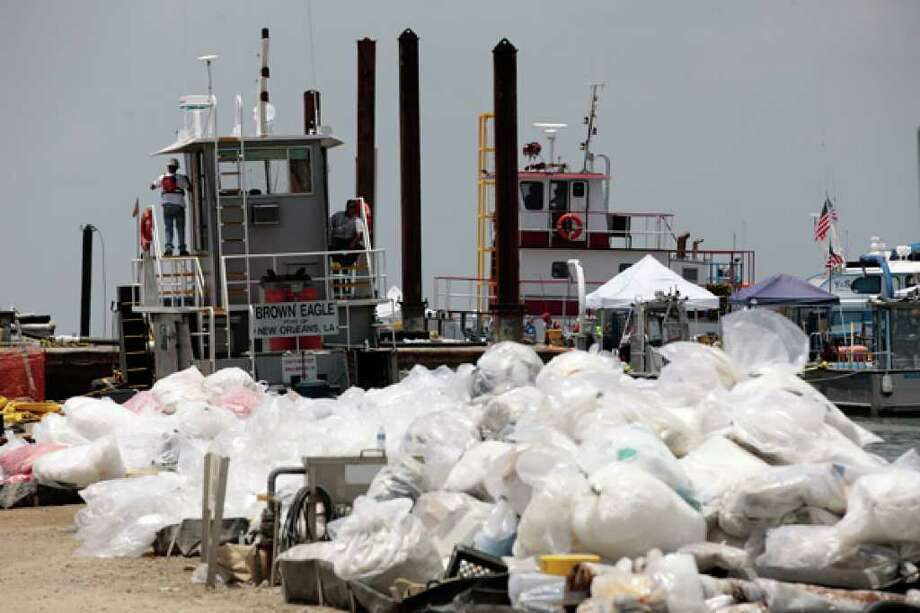 Piles of dirty oil retention booms await disposal at a staging area in Grand Isle, La. More than 50,000 tons of boom and oily debris have made their way to landfills or incinerators, federal officials said.
