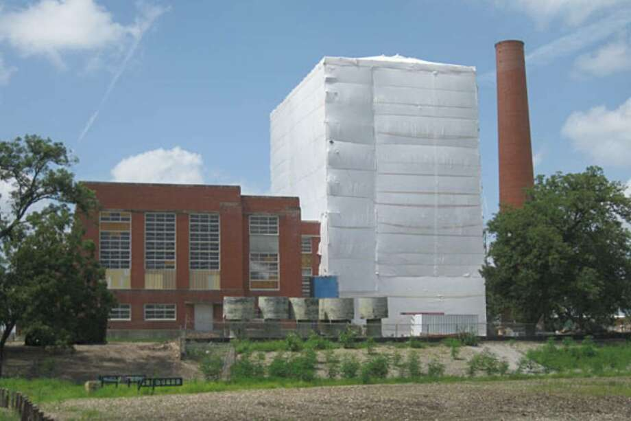 A giant white sheet hangs over part of Mission Road Power Plant as renovations are underway for what CPS Energy hopes will be a facility including condos, shops and parks. Th e sheet covers possible lead paint contamination as the building is shelled.