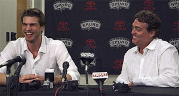 Tiago Splitter (left) laughs at a press conference Monday at the Spurs practice facility with Spurs general manager R.C. Buford.