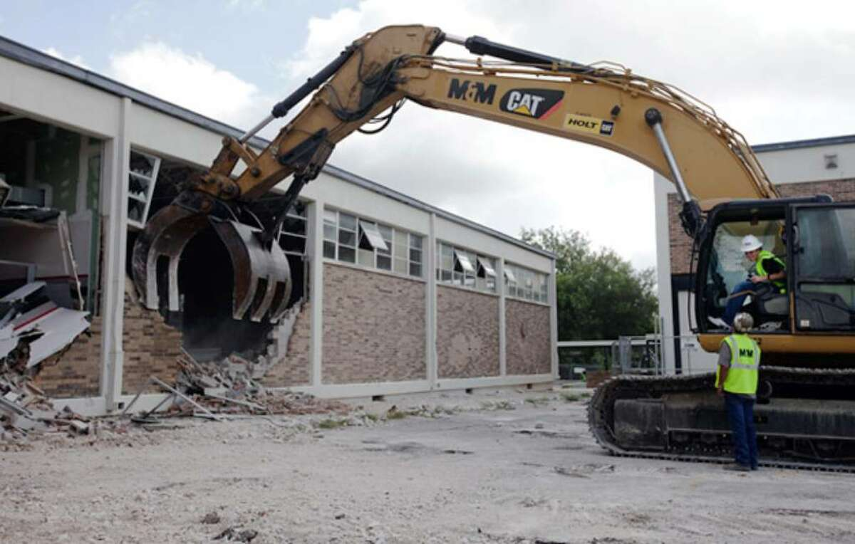 Churchill High School senior Warren Truesdale sits in the cab of a 54-ton excavator and knocks down a wall of the old gym. His parents bid $600 to win the chance for him and his sister to take the first swings at bringing down the building.