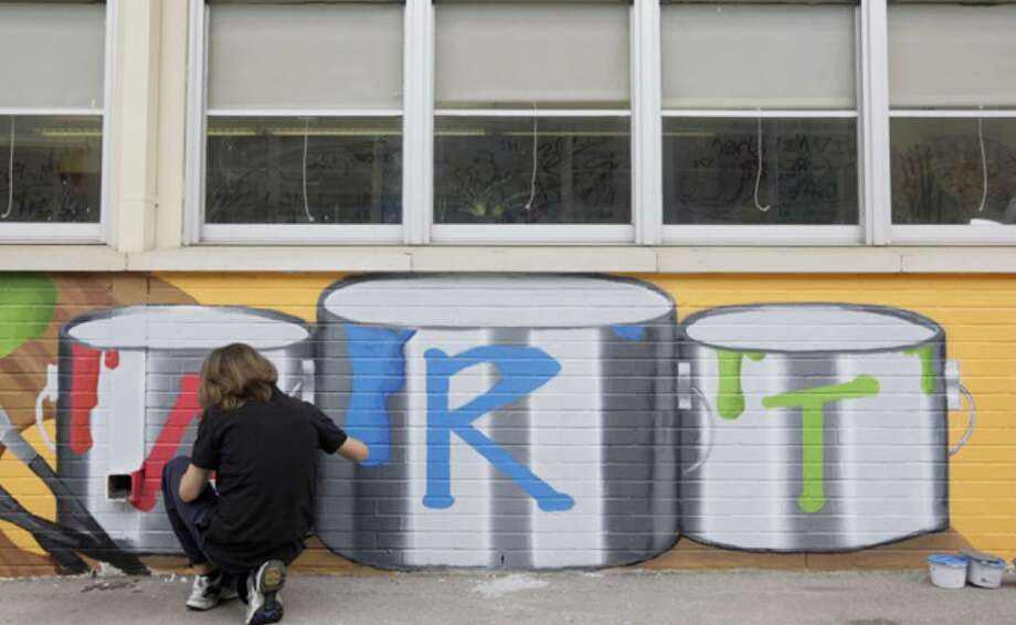 Nicholas Chavez, 15, adds detail to part of a mural at the Henry Ford Academy: Alameda School for Art + Design.