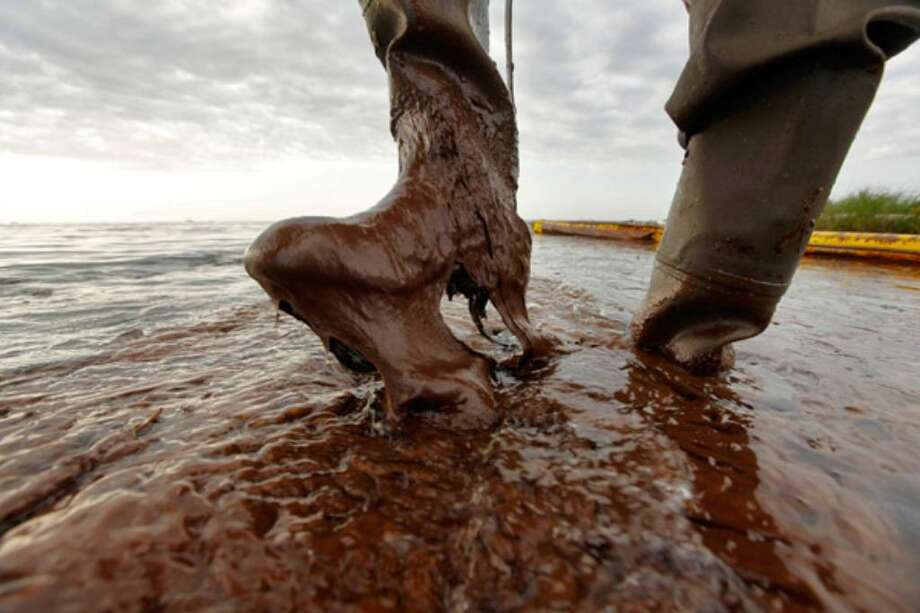 Plaquemines Parish coastal zone director P.J. Hahn lifts his boot out of thick beached oil at Queen Bess Island in Barataria Bay, just off the Gulf of Mexico in Plaquemines Parish, La.