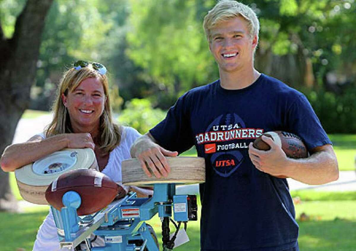 UTSA receiver Jake Wanamaker and his mom, Kelly, hang onto Jake's graduation present, the Jugs Field General football passing machine.