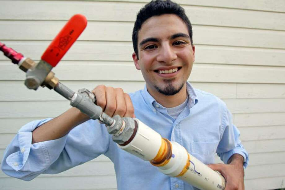 Thomas Villalon Jr. holds a compressed-air cannon he made at home. A top graduate of Central Catholic High School, he's headed for MIT this fall.