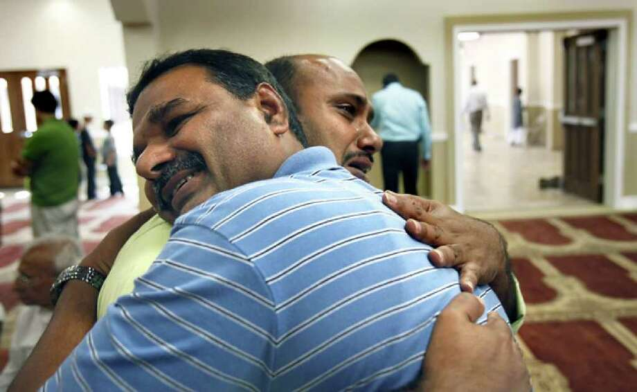 Sharif Khan (right) cries tears of joy as he hugs Anis Syed during the opening of Al-Madinah Mosque, with first Friday of Ramadan prayers lead by Imam Ameen Aziz.