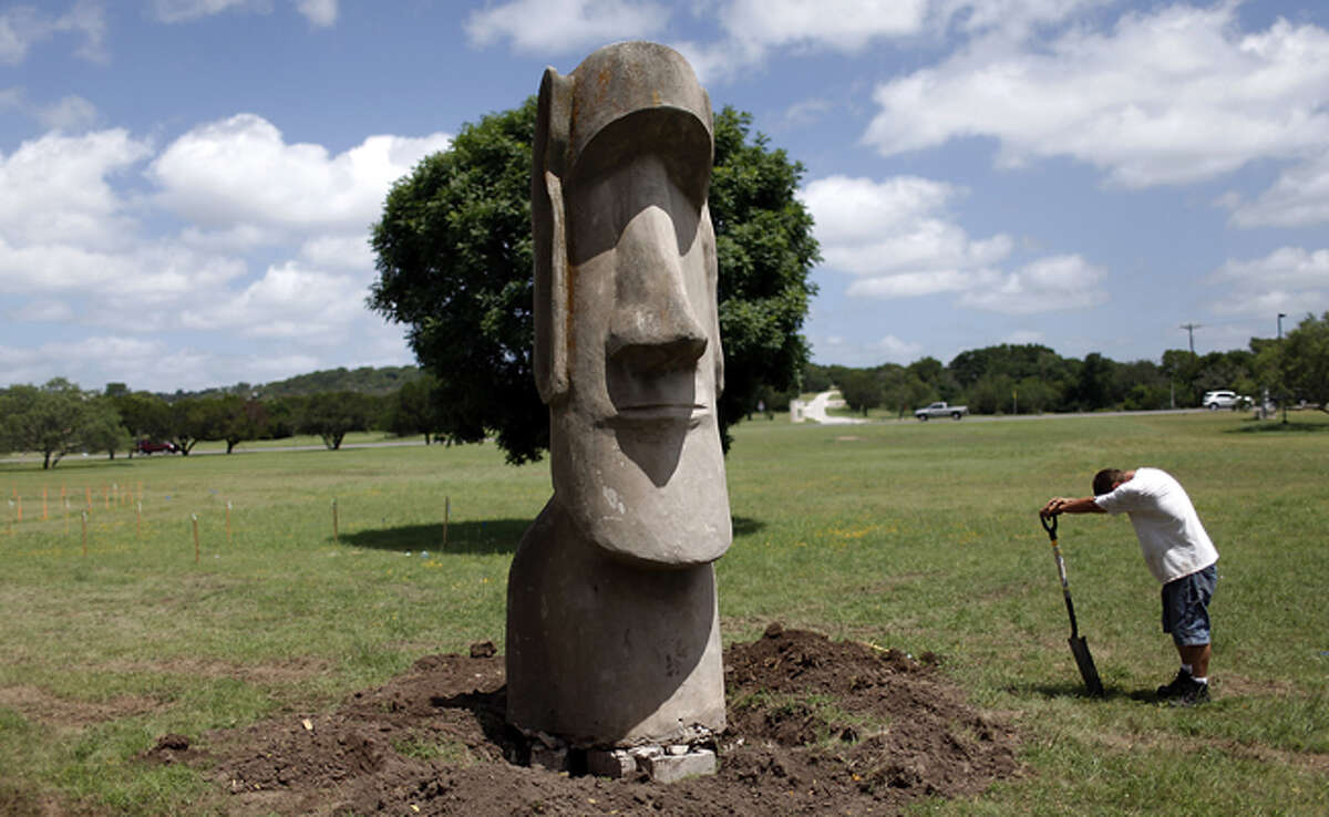 Adam Koehnke takes a moment to rest as he digs around one of the Easter Island replicas. The giant head is made of plaster and rebar. It weighs about 1,200 pounds.
