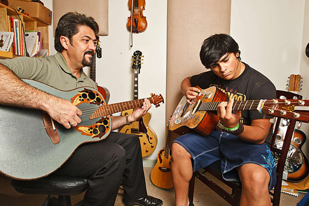 Bobby Flores, owner of The Bulverde Academy of Music, gives a guitar lesson to Garrett Escalante.