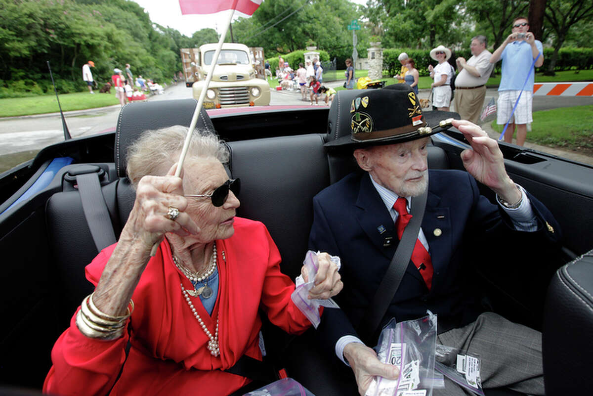 Retired Army Col. A.T. Pumphrey (right) acknowledges the parade crowd while serving as grand marshal in the Terrell Hills Independence Day Parade on Saturday, July 3, 2010. Pumphrey was joined by his wife, Angela, at his side. Pumphrey, 93, had served in Army Aviation from World War II to Vietnam.