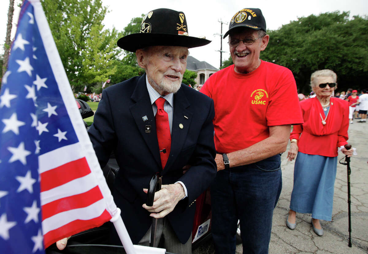 Retired Army Col. A.T. Pumphrey (center) is greeted by Johnny Purnell after completing a ride as grand marshal.
