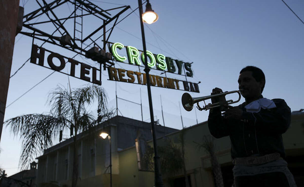 Juan Rangel of Mariachi Acuña looks for work with other members of the group at Crosby's, which caters to U.S. tourists, in Ciudad Acuña, Mexico. The group didn't find any customers to play for and went to another restaurant.