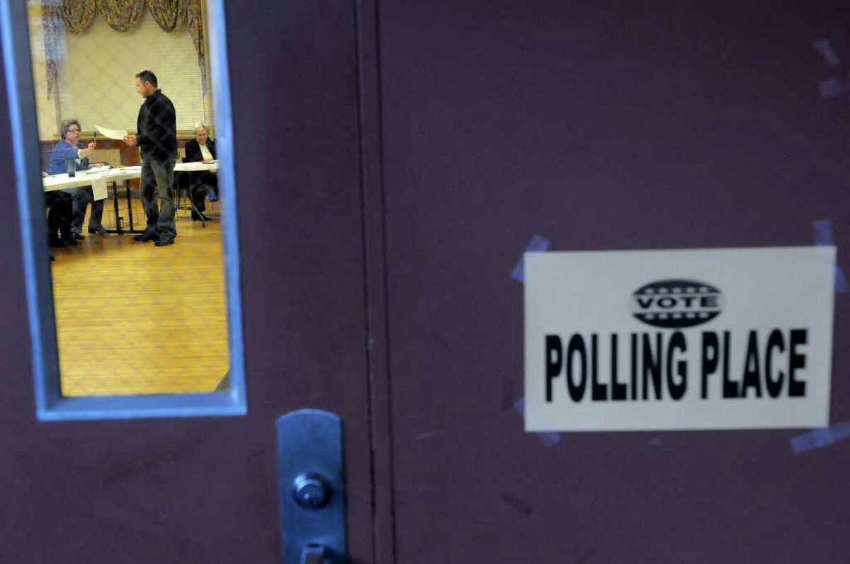 A voter receives his ballot Tuesday at the polling station in the Open Bible Baptist Church in Rensselaer. (Paul Buckowski / Times Union)