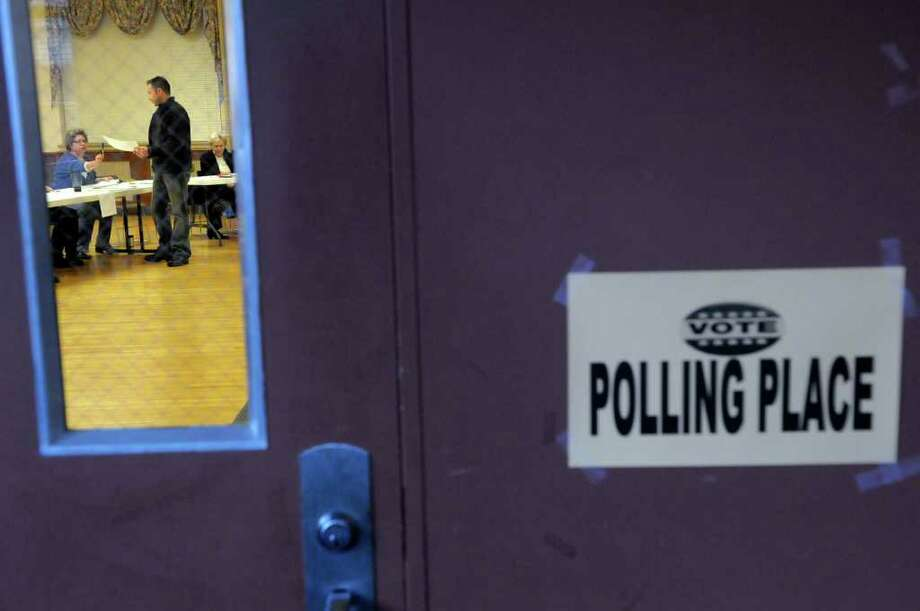 A voter receives his ballot Tuesday at the polling station in the Open Bible Baptist Church in Rensselaer.  (Paul Buckowski / Times Union) Photo: Paul Buckowski / 00010822A