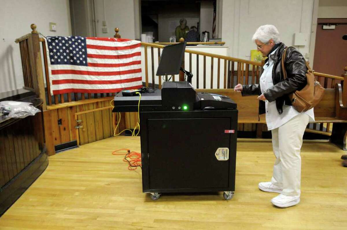 Dawn Bentley Wilson waits to see the message that her vote has been cast after she inserted her paper ballot into the scanner Tuesday at the polling station in the Open Bible Baptist Church in Rensselaer. (Paul Buckowski / Times Union)