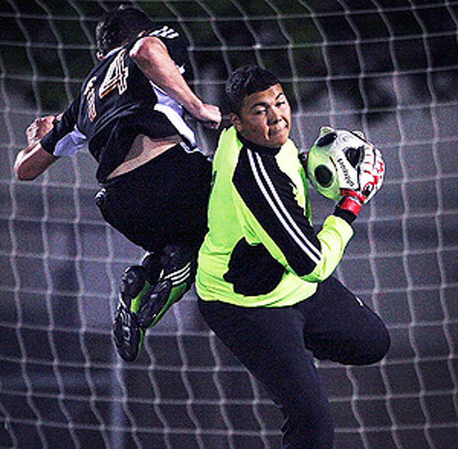 Jefferson goalkeeper Juan Moreno, who had seven saves, grabs the ball to prevent Medina Valley's Zane Watson from reaching it as he flies past. / © 2010 San Antonio Express-News