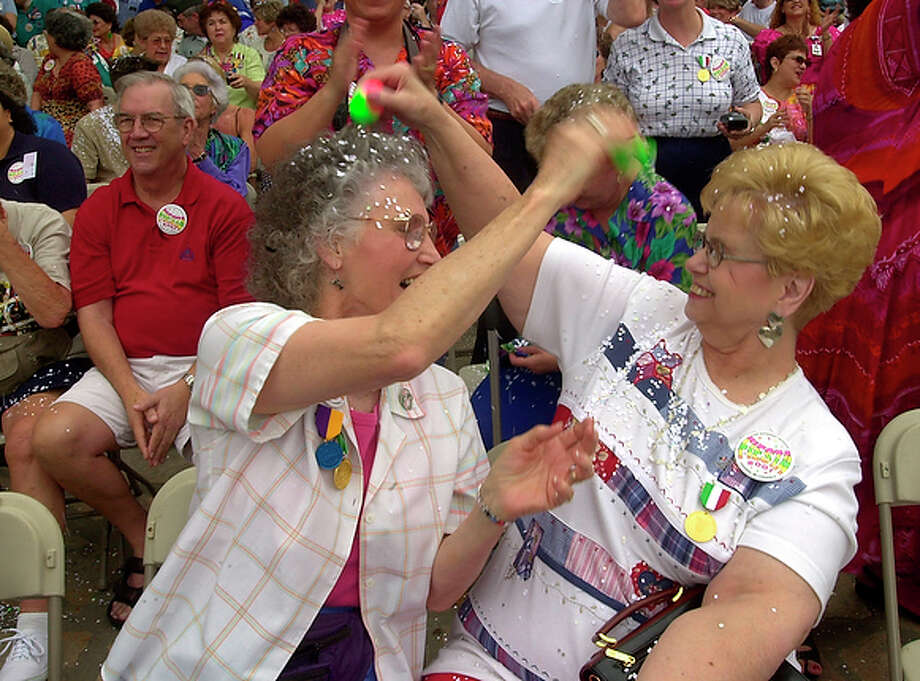 Patricia Voorhees of Conroe and Shirley May of San Antonio abandon the traditional method of cracking cascarones on someone's head in favor of pouring out the confetti. / EN