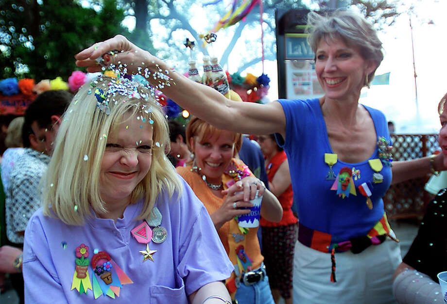 Deborah Payeur of Ohio grimaces as her friend Jackie Mitchell of New Braunfels smashes a cascaron on her head while attending Night in Old San Antonio in 2000. / en