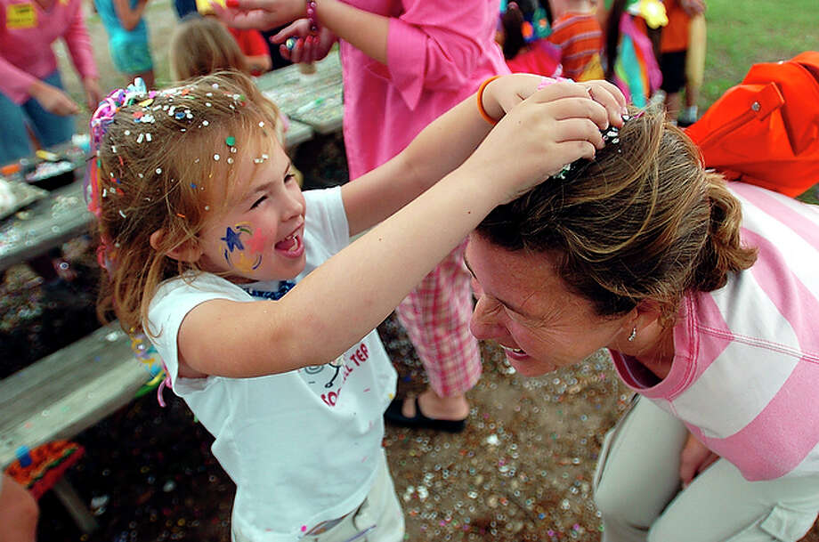 Kathryn Ellwood laughs as she cracks a cascaron on the head of her mother, Molly, at Howard Early Childhood Center's mini-Fiesta in 2004. / SAN ANTONIO EXPRESS-NEWS