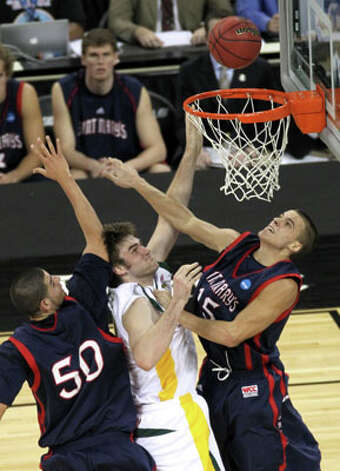 Baylor center Josh Lomers (50) shoots a layup between Saint Mary's center Omar Samhan (50) and forward Beau Levesque (15) on March 26. Lomers had six points in the win. Lomers leaves Baylor as the school's career leader in field-goal percentage (66.3) and first in victories (82 to Tweety Carter's 81). / Houston Chronicle