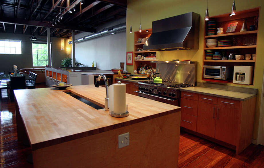 The kitchen has a large island with an unusual channel sink in the center. A six-burner stainless stove with a vent hood serves as another focal point in the kitchen. Beyond the kitchen are the dining and living areas. / jdavenport@express-news.net