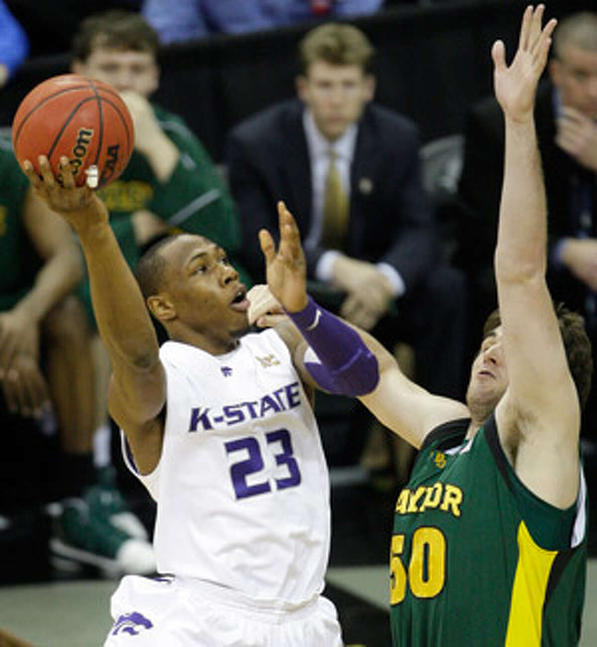 Kansas State's ever-in-motion forward Dominique Sutton, in action against Baylor in the Big 12 tournament, performs a little out of the spotlight so his team has a chance to shine in it.
