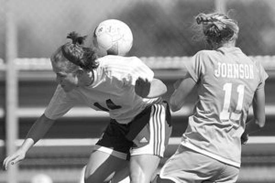 There was a time when Reagan's Georgia Mullins (left) and Johnson's Sharis Lachappelle, battling for a ball during a recent match at Blossom Soccer Stadium, were teammates at Reagan.