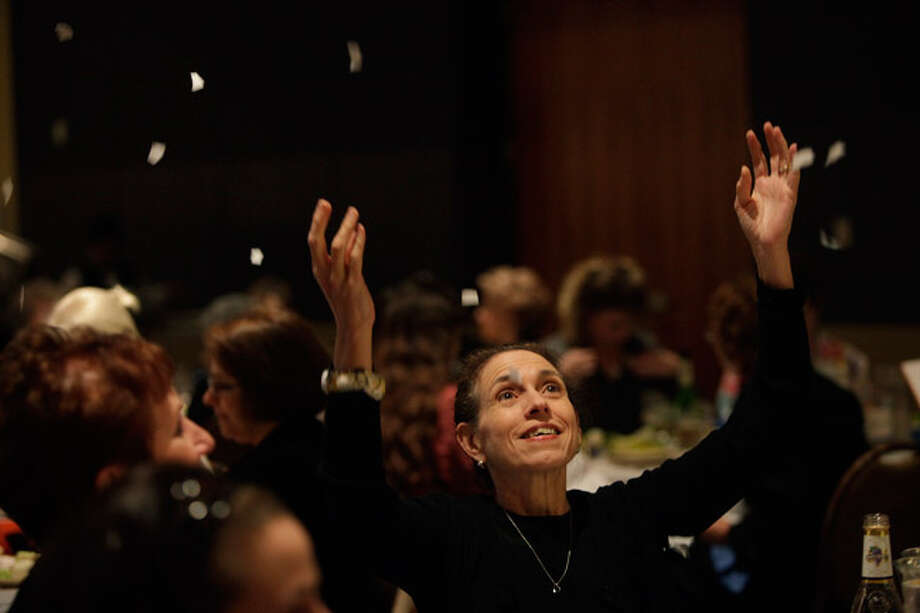 After writing down the things that hold them back, then ripping up the papers, Lauren Hughes and the other women at the 10th annual Women's Seder in Temple Beth-El's Barshop Auditorium throw the pieces into the air. More than 100 women attended the event Tuesday.