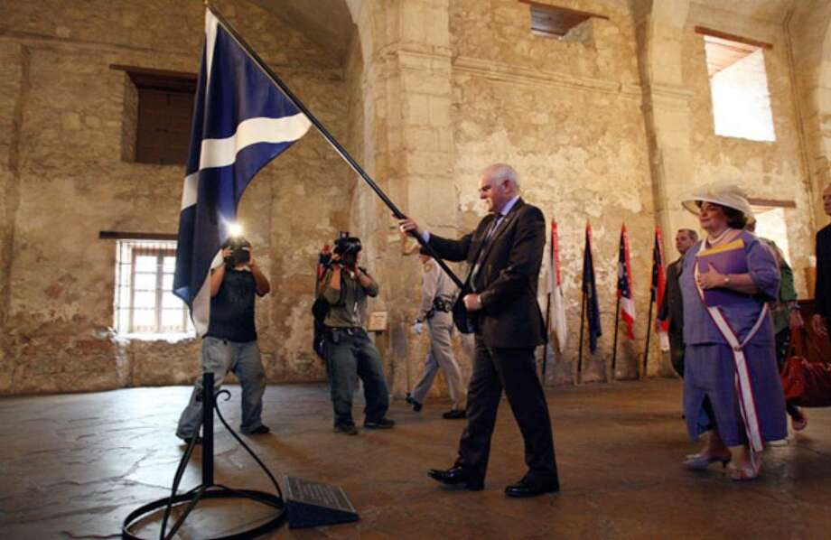 """Jim Mather, Scotland's minister for tourism, places his nation's flag near the stone honoring the four known Scots who fought at the Alamo, which he said symbolizes an """"unquenchable thirst for independence"""" shared by Scotland and the U.S."""