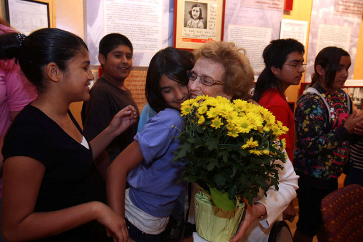 Director Maxine Cohen (holding flowers) gets a hug from Alexis Macias, 11, from Navarro Intermediate School in Geronimo, at the Holocaust Memorial Museum of San Antonio.