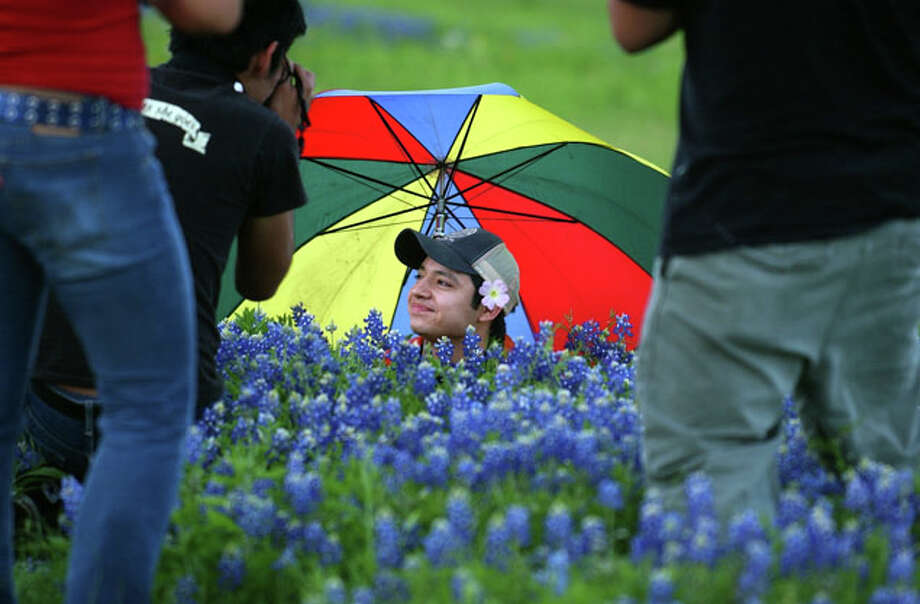 "San Antonio College Photo One student Sam Solis poses in the bluebonnets so Fabian Villa can take ""cheesy bluebonnet pictures"" for extra credit in his color photography class on Highway 281 on Wednesday April 7, 2004 in San Antonio. Photo students Sarah Arguijo, left, and Steven Casanova, right, also shoot the scene. / SAN ANTONIO EXPRESS-NEWS"
