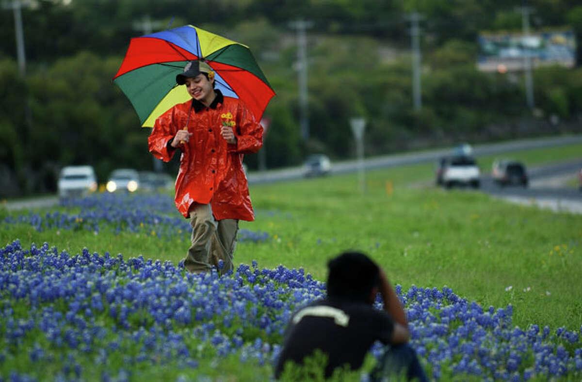 San Antonio College Photo One student Sam Solis skips through bluebonnets so Fabian Villa can take