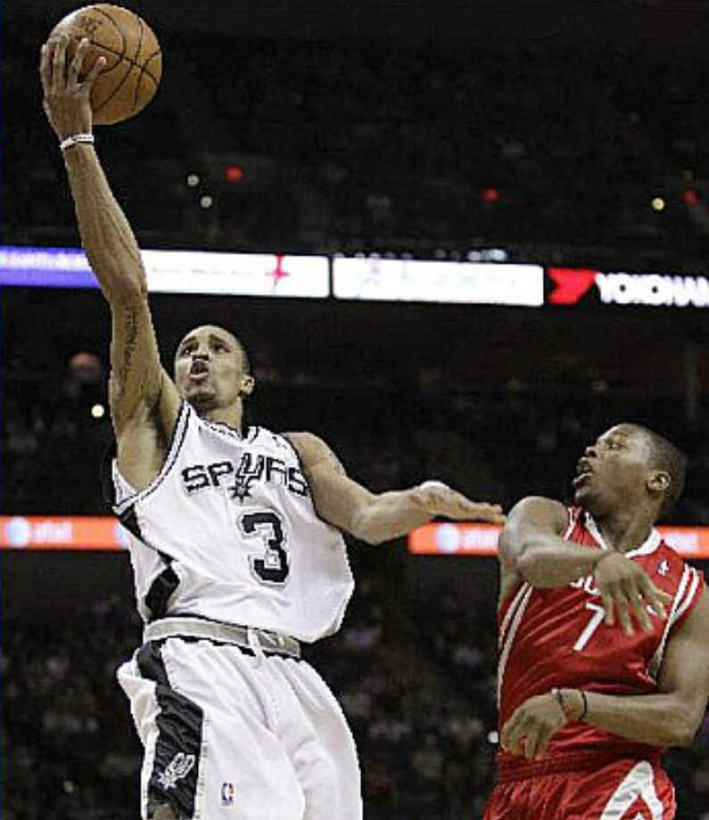 George Hill goes to the basket past Houston's Kyle Lowry during the first quarter. The Spurs guard, playing the point in place of Tony Parker, scored 30.