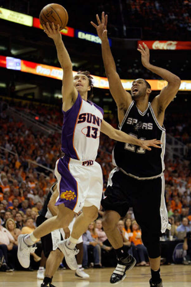 Phoenix's Steve Nash drives to the basket for two of his 33 points Monday night, with the Spurs' Tim Duncan in pursuit.