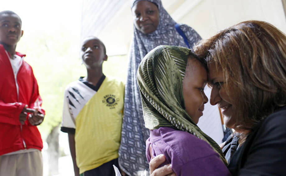 Pam Espurvoa (right) greets Head Start student Sadia Waliyow, 4, as Sadia's mother, Hawa Hassan (background, right) watches.