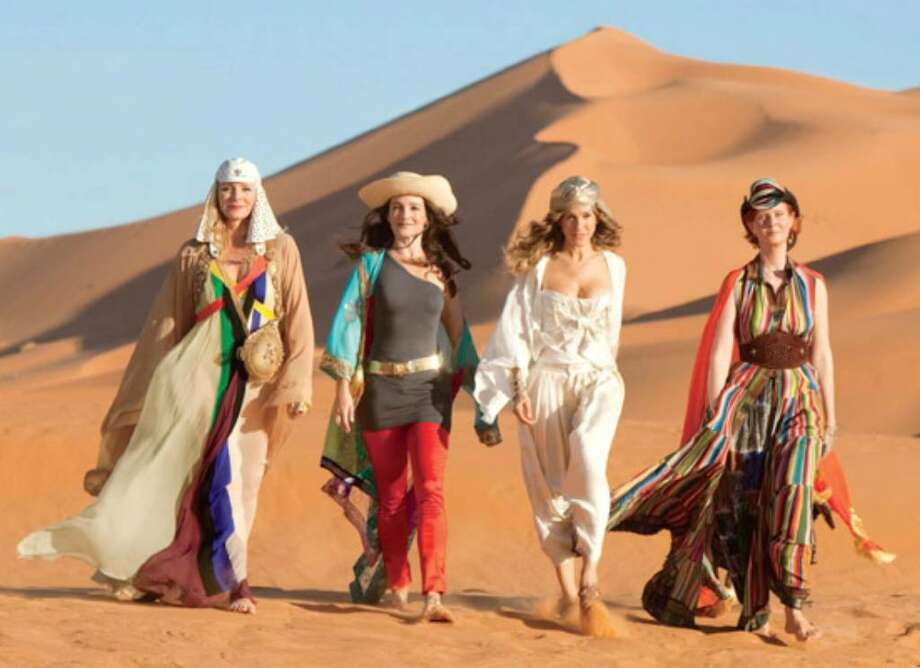 Kim Cattrall, from left, wears a Jean Paul Gaultier dress with a Balizza wrap and Horst hat (bag from Ralph Lauren); Kristin Davis wears an asymmetrical Alexander Wang top, Zac Posen pants and Bill Blass belt; Sarah Jessica Parker wears a Dior bustier over Ralph Lauren harem pants, Zara blouse and Philip Treacy turban; Cynthia Nixon wears a matching Hermès hat and dress with a Roberto Cavalli belt.