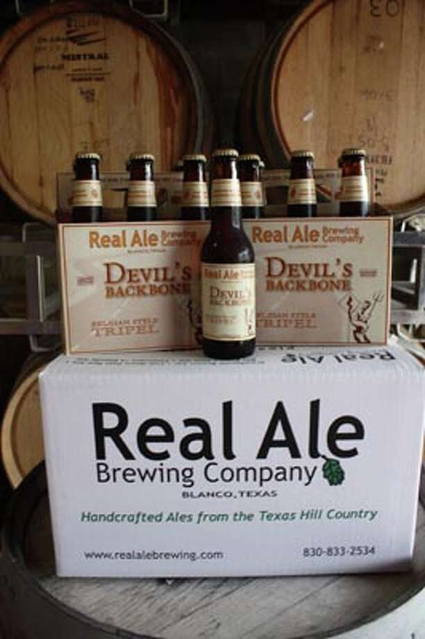 Bottles of Devil's Backbone, a Belgian-style Tripel from Real Ale Brewing in Blanco, sits in front of wood barrels used to age some of their beers including a version of Devil's Backbone called Devil's Share.