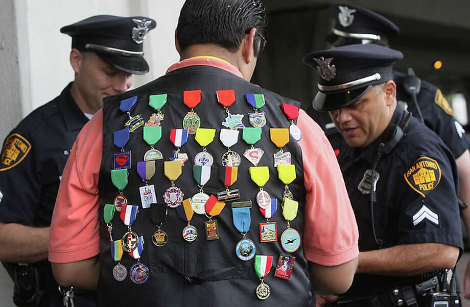 Edward Mireles, center, sports his collection of medals as he gives some out to San Antonio police officers. / SAN ANTONIO EXPRESS-NEWS